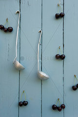 Cherries and two laddles hanging on wooden wall