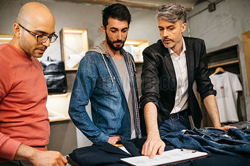 Casual man standing in boutique with stylists and discussing new modern outfit in team