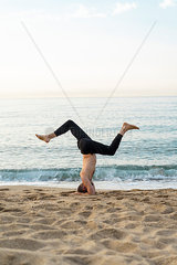 Spain. Man doing yoga on the beach in the evening