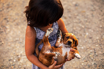 Girl holding puppy in her arms