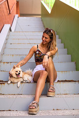 Pretty young woman smiling  caressing a dog