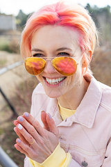 Portrait of young laughing woman  sun glasses and pink jeans jacket
