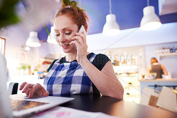 Smiling young woman working in a cafe using laptop and cell phone
