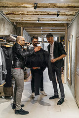 Designer and stylist in modern menswear shop offering new collection to man