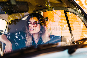Young woman wearing sunglasses sitting in a car