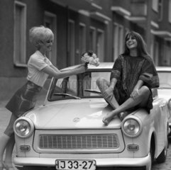 Berlin  DDR  Modeaufnahme  Modefotografie  junge Frau reicht ihrer auf einem Trabant sitzenden Freundin Blumen