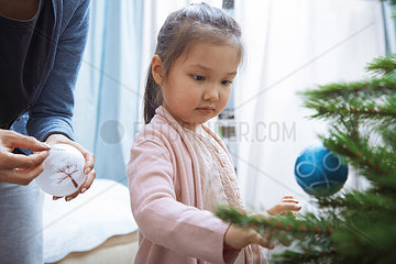 Portrait of little girl decorating Christmas tree with her mother