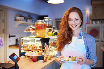 Portrait of smiling young woman serving cake in a cafe