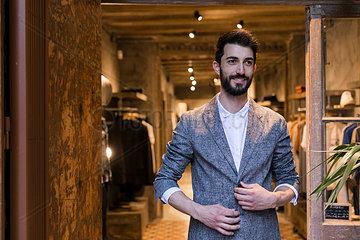 Portrait of smiling man wearing jacket leaving menswear shop