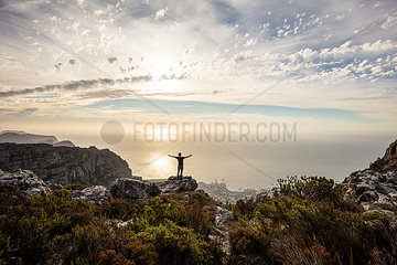 South Africa  Cape Town  Table Mountain  man standing on a rock at sunset