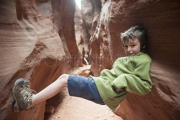 Boy balancing in narrow slot canyon