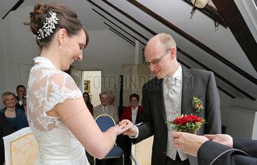 Buckow  Deutschland  Braeutigam steckt seiner Braut bei der standesamtlichen Trauung den Ring an