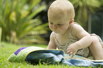 Baby sitting on blanket outdoors
