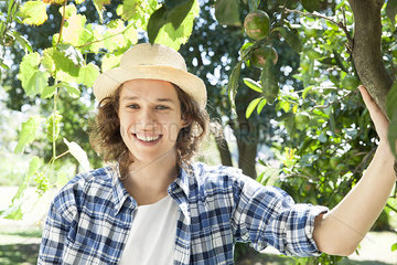 Young man standing under tree in vineyard  portrait