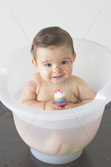 Baby sitting in bath with tube of colorful soap