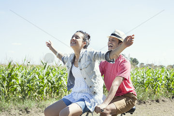 Couple riding bike together  woman with arms outstretched