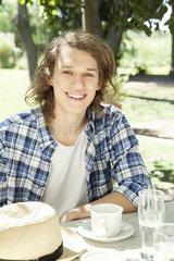 Young man enjoying coffee outdoors