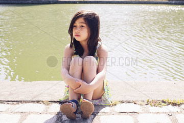 Girl sitting by pond in park  looking away in thought