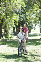 Young couple riding bicycle together with girlfriend seated sidesaddle on crossbar