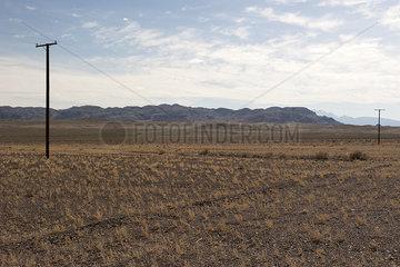 Power lines running through arid landscape