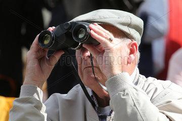Paris  Frankreich  Mann schaut durch sein Fernglas