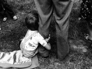 Junge klammert sich an Vaters Bein