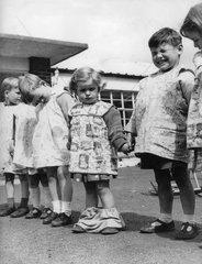 Kinder stehen Hand in Hand - Maedchen verliert Hose