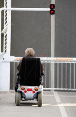 Kappeln  Mensch im Rollstuhl vor Schranke und roter Ampel