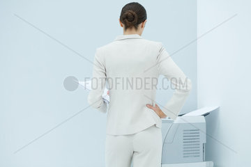 Businesswoman standing with hand on hip  looking at printer  rear view