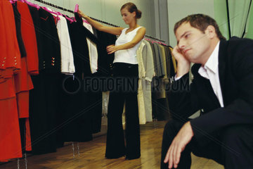 Woman shopping for clothes  bored man waiting in foreground