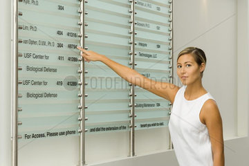 Woman pointing at building directory  looking at camera