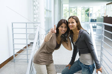 Woman standing on stairs with daughter  pointing  both looking up and smiling