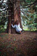 Frau hockt hinterm Baum