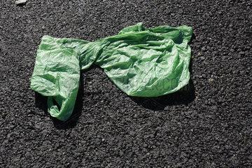 gruene Plastiktuete auf Asphalt
