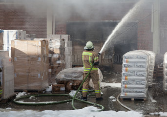 Berlin  Deutschland  Feuerwehrmaenner bei Loescharbeiten