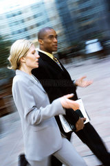 Businessman and businesswoman walking together in conversation