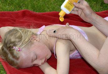 Maedchen wird mit Sonnencreme eingerieben