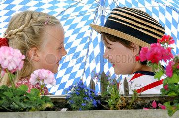 zwei bayerische Kinder unter Sonnenschirm