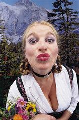 Hamburg  Deutschland  Frau im Dirndl macht einen Kussmund