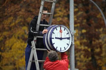 Berlin  Deutschland  Zwei Maenner befestigen eine Uhr der DB