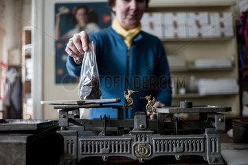 Berlin  Deutschland  Verkaeuferin im Laden der Erich Hamann KG wiegt Schokolade ab
