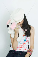 Teenage girl hiding face with stuffed toy  laughing