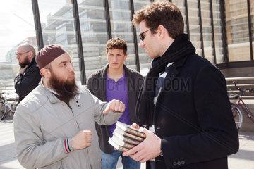 Berlin  Deutschland  Salafist diskutiert mit Passant  der einen Stapel von Koran-Exemplaren haelt
