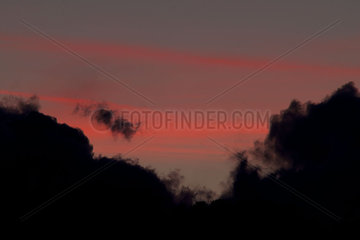 Clouds silhouetted against colorful twilight sky