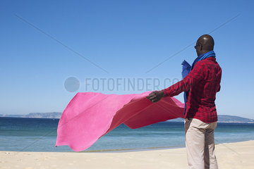 Man at the beach  holding blanket in the breeze