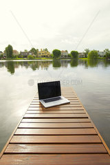 Laptop computer on lake pier