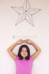 Girl standing beneath star decoration  daydreaming  portrait