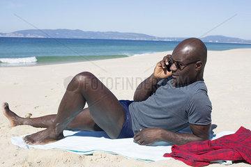 Man lying on beach  talking on cell phone