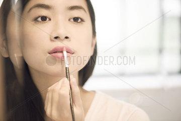Woman using lipbrush to apply lipstick
