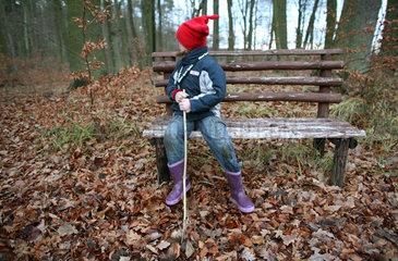 Prangendorf  Deutschland  Maedchen sitzt auf einer Bank und sieht sich suchend um